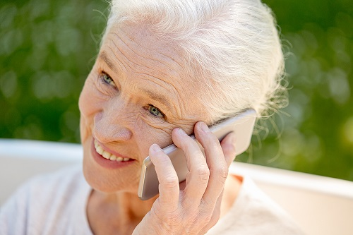 happy senior woman calling on smartphone in summer